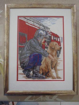 trés jolie broderie représentant un sapeur pompier et son chien prés du camion réalisée au point de croix sur une toile aïda avec un encadrement professionnel argenté.    - 15983980