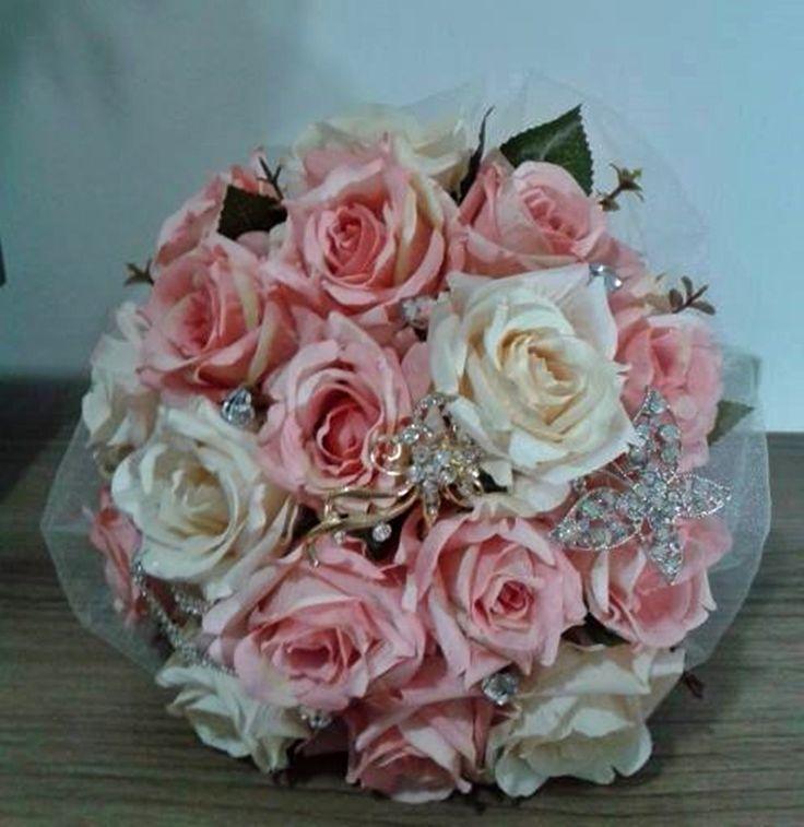 """Buquê Paris (design único e exclusivo Pretty Art) <br> <br>Composto de rosas artificiais em tom pastel (salmão e bege), broches em tons de prata e dourado cravejados em strass e pontos de luz. <br>, Haste com tule francês com leve brilho, cetim e renda vintage. <br> <br>Medidas <br>22cm largura e 30cm altura. <br> <br>A escolha do buquê de noiva é tão importante quanto a escolha do vestido. <br> <br>O """"Bouquet de Broches"""" é uma verdadeira semi jóia"""