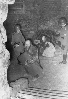 Lublin, Poland, German policemen removing Jews from a hiding place in the ghetto.