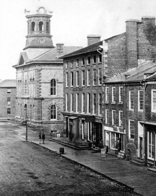 An early photograph of King St. at Market St. in Brockville, ON  --  1866   The main buildings shown are the 'Victoria Hall' (on the left), and the Revere Hotel (in the centre).  The photographer was probably Alexander C. McIntyre.