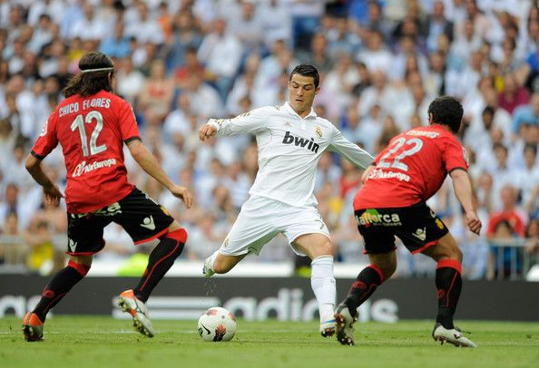 Cristiano Ronaldo Photos Photos - Cristiano Ronaldo (C) of Real Madrid CF is challenged by Chico Flores (L)  and Cendros of RCD Mallorca during the La Liga match between Real Madrid CF and RCD Mallorca at Estadio Santiago Bernabeu on May 13, 2012 in Madrid, Spain. - Real Madrid CF v RCD Mallorca  - Liga BBVA
