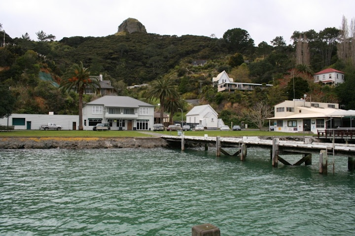 Whangaroa Harbour Village.  Left to right: Marlin Hotel, Local Community Hall, Sportfishing Club. St Pauls Rock looking down on the Village.