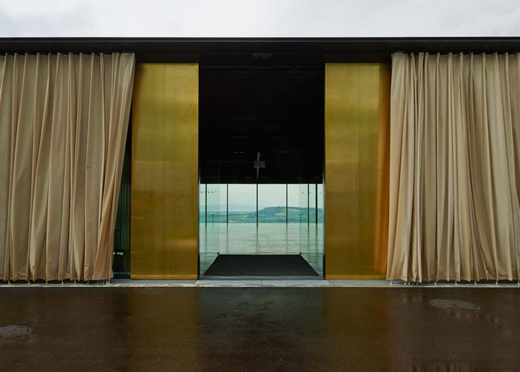 Alpine events venue featuring glass walls with golden outdoor curtains.