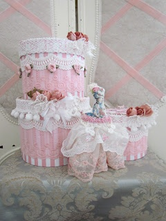Pink cream cake, without the calories..  Four carton boxes stacked on top of each other  decorated with delicious lace and flowers.