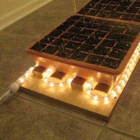 Christmas rope lights to make Heat Mat for seed starting--brilliant and frugal gardening DIY!  Gentle bottom heat really kick starts your seedlings!