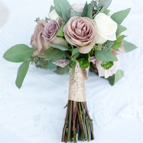 Amnesia roses accented by seeded eucalyptus leaves gave Hilary's delicate bridal bouquet a vintage air. A satin bouquet wrap with pearl details and a bow made with Liberty London fabric added a soft feminine touch.