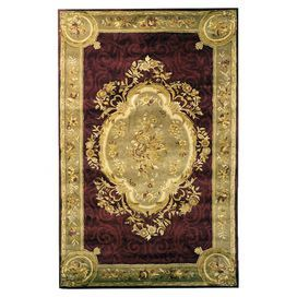 Handmade wool rug with a scrolling medallion motif and carved details.  Product: RugConstruction Material: 100% WoolColor: Maroon and beigeFeatures: Hand-tufted Note: Please be aware that actual colors may vary from those shown on your screen. Accent rugs may also not show the entire pattern that the corresponding area rugs have.Cleaning and Care: Professional cleaning recommended