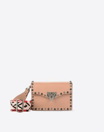 Are you looking for Valentino Garavani Guitar Rockstud Rolling Small Cross Body Bag? Find out all the details at Valentino Online Boutique and shop designer icons to wear.