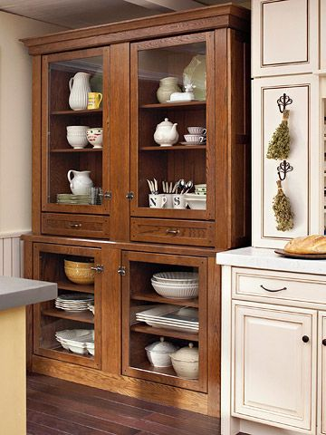 An antique China hutch inspired the look of this storage piece made from ordinary kitchen cabinetry.