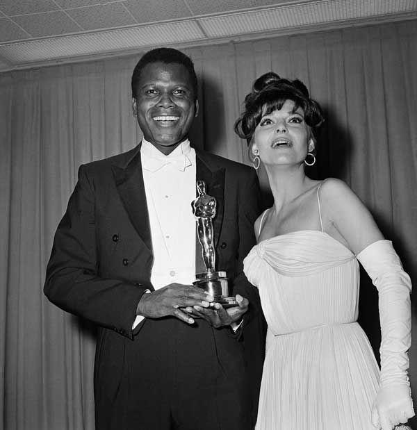 IlPost - 1964 - Sidney Poitier, I gigli del campo. Nella foto, Poitier viene premiato da Anne Bancroft. (AP Photo)