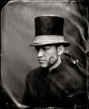 Young Maori gentleman, who has quite a finely chiseled profile, in top hat with a silk band.