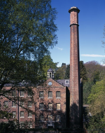 The Chimney and Bell Tower at Quarry Bank Mill, Cheshire, with woodland in the background. National Trust - Dennis Gilbert