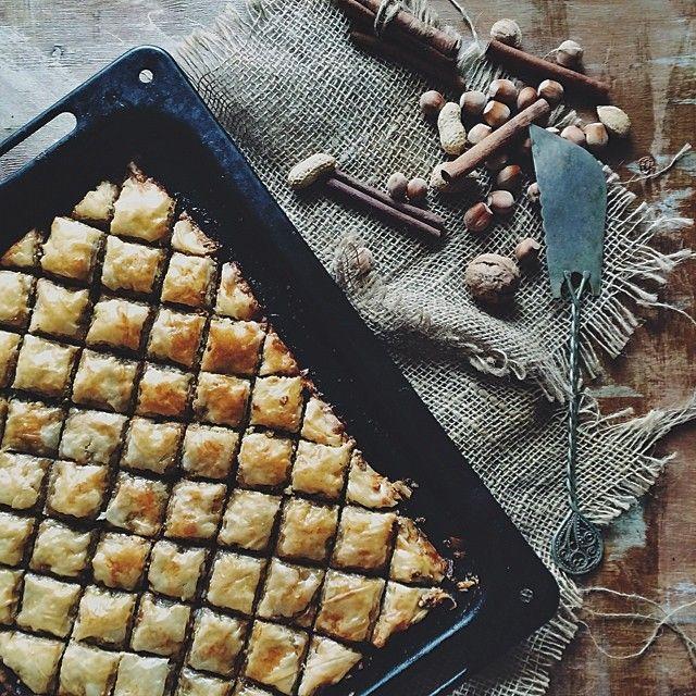 Ингредиенты: • по 100 г грецких орехов, миндаля, фисташек • 2 ч ложки корицы • 2 ч ложки молотой гвоздики • 200 г растопленного сливочного масла • 450 г фило-теста. Для медовой смеси: Мёд 50 г на 100 мл теплой воды. Сироп: • 300 г тростникового сахара • 150 мл меда • 2 палочки корицы • 2 широких или 4 узких полоски апельсиновой цедры