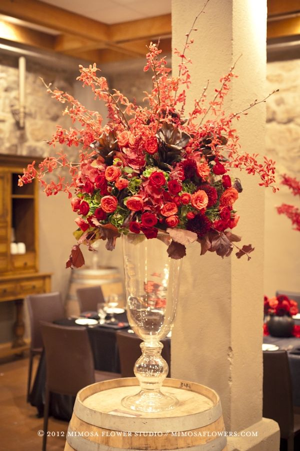 Large floral arrangement on a wine barrel with red orchids...stunning!