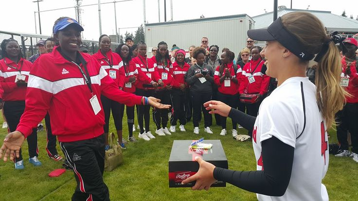 White Sox player Gillian Wills presents new cleats to a player from Kenya at the Women's World Championships, 2016.