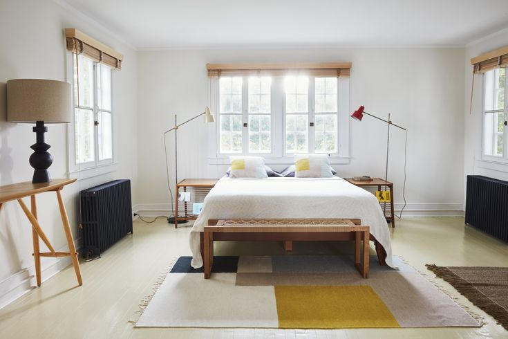 In the owners' bedroom on the second floor, the pale yellow floor paint is original; Valentin painted the radiators in dark slate as a contrast. The color-blocked rug is the Large Kelim Rug from Ferm Living. Same goes for the throw pillows, which are the Ferm Living Kelim Cushions. The two vintage floor lamps were restored and rewired by Holler & Squall in Brooklyn. The vintage side tables were sourced at Esoteric Survey in San Diego and the bench at the foot of the bed is custom by Cate…