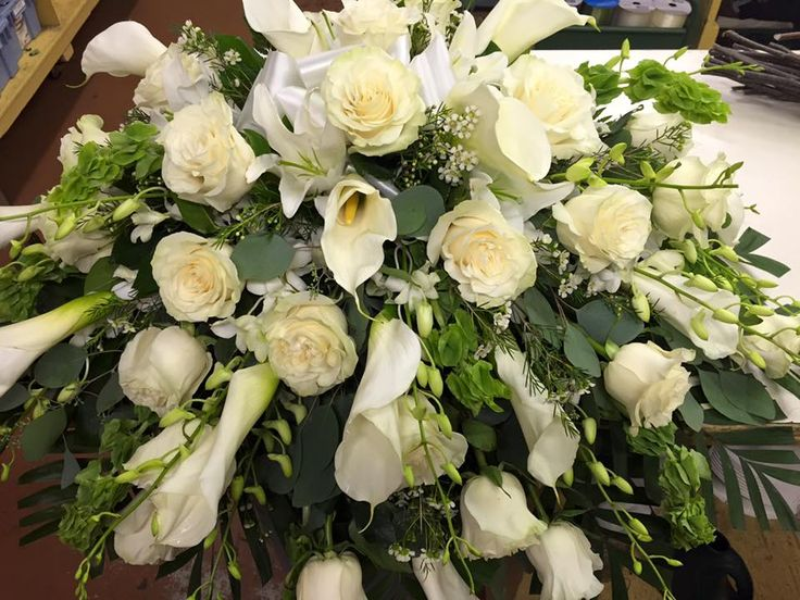 Casket spray white roses, white calla lillies and white orchids.