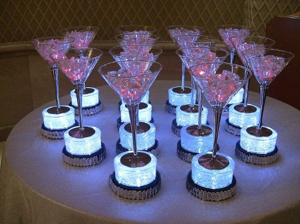 Fabulous theme party decor centerpieces, featuring martini glasses on light bases, filled with faux ice.