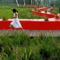 The Red Ribbon Park in China's Qinhuangdao City by Turenscape Landscape Architects winds along a verdant riverside