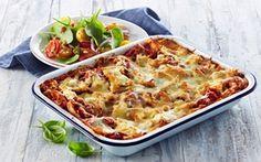 Lækker lasagne med pulled chicken og hytteost, der strutter af smag og sundhed - serveret med farverig tomatsalat på en bund af spæde spinatblade.