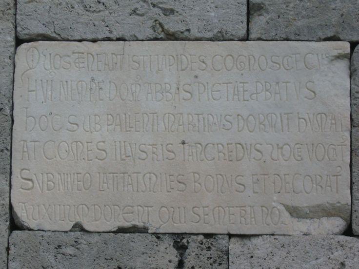 Abbazia di San Savino, iscrizione sulla lapide funeraria inserita tra i blocchi di calcare della parete laterale