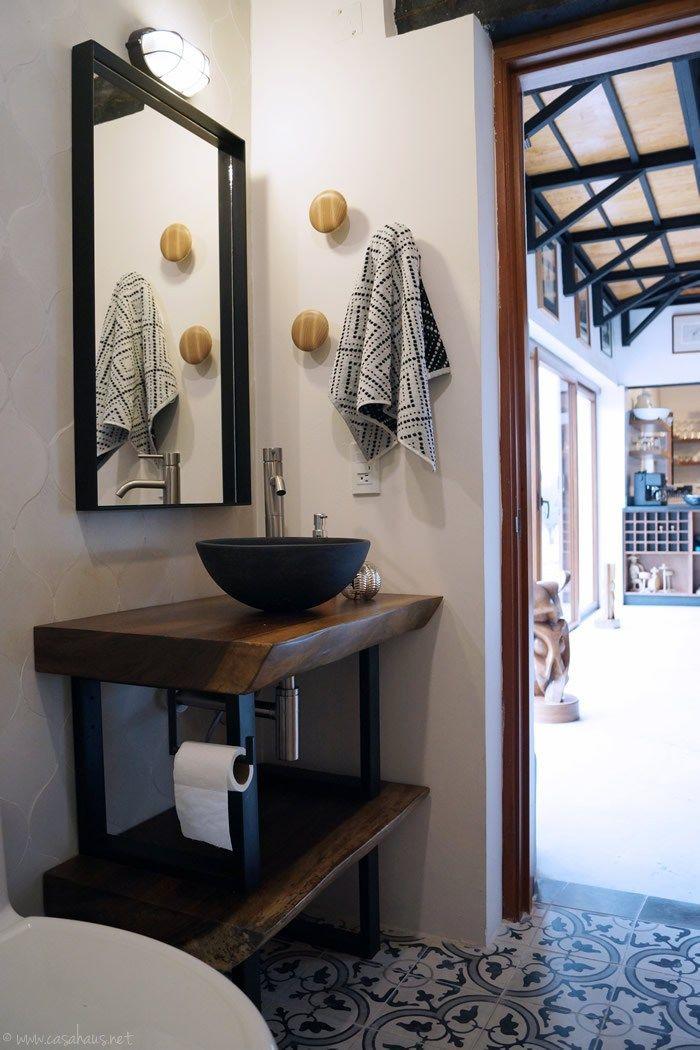 Une petite salle de bains esprit rétro avec carreaux de ciment au sol, meuble de métier, vasque noire moderne et grand miroir pour agrandir visuellement l'espace.
