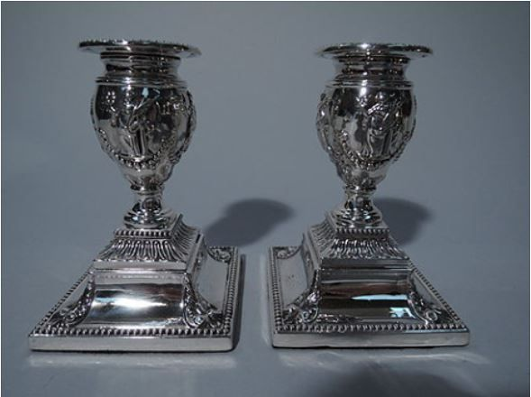 Pair of Classical English Sterling Silver Candlesticks 1880 BO425 Pair of Classical sterling silver candlesticks. Made by Robert Harper in London in 1880. Vase socket with low-relief draped female figures and beaded garland. Detachable bobeche with beaded rim. Socket mounted to foot, which in turn is mounted to stepped square base with foliage and beading. A striking design in small scale. A great housewarming or wedding gift. Hallmarked. Only one pair in stock.
