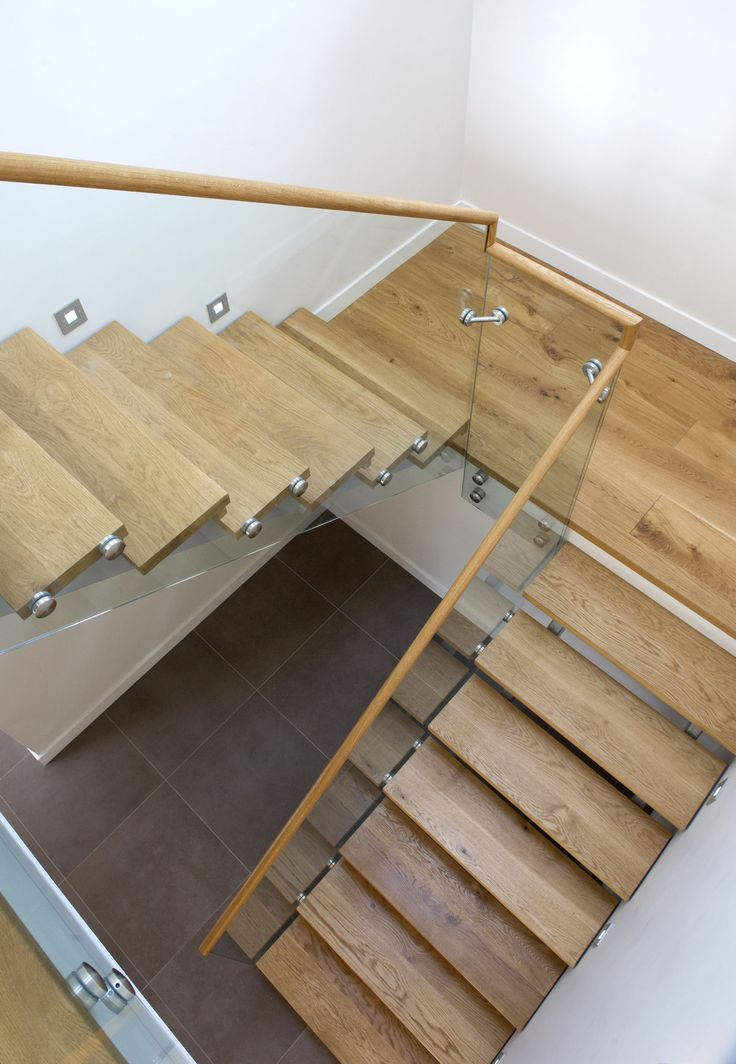 Architects The Bazeley Partnership designed this replacement 5-bedroomed California inspired house to sit on the side of a steep coastal valley in North Cornwall. Staircase, wood stairs, glass balustrade, wooden hand rail.