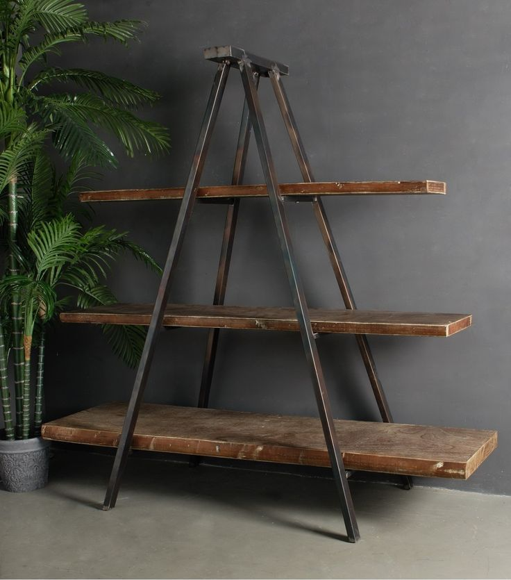 Whether your style is Manhattan Loft or rustic country, our Industrial Tripod Bookcase has the casual charm to blend seamlessly with a range of looks. Featuring an industrial style metal frame and timber shelves it can function as book shelves, or generous display area for crockery and collectibles. Its two sided design allows for use as a room divider.  	NB: Please enquire for finish to shelves as each piece will vary