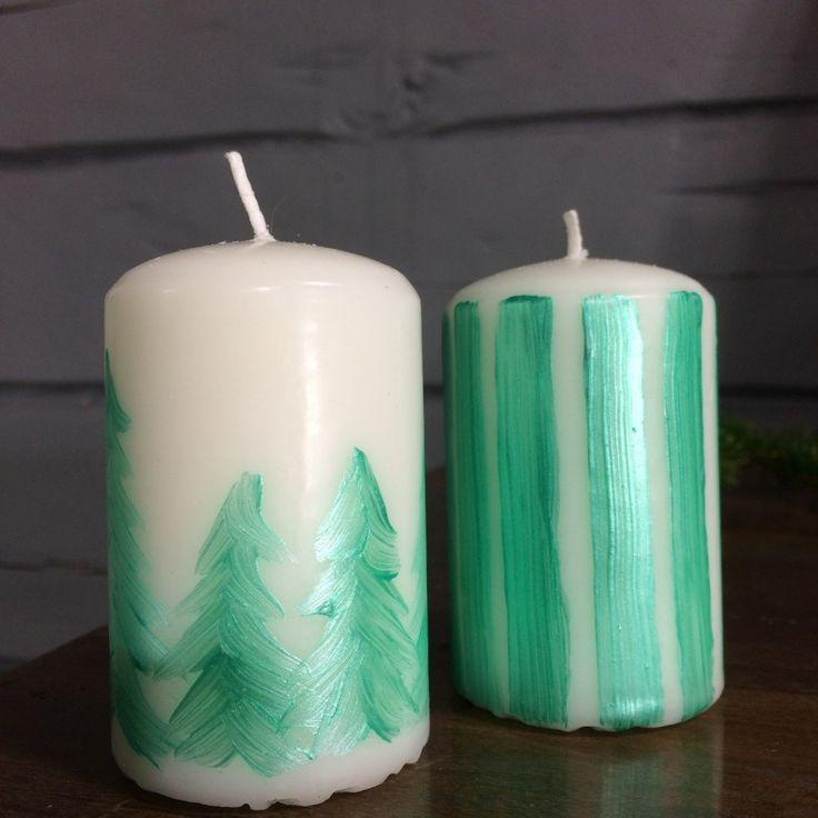 två vita blockljus det ena med mönster målat som gröna granar och det andra med målade gröna ränder.