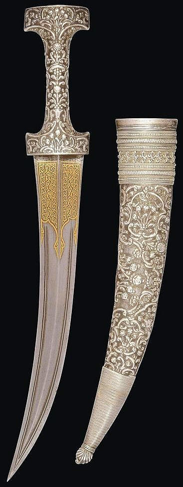 Ottoman jambya, 18th to 19th century, tapering double-edged blade curving upward, each face with central ridge, the forte with gold overlaid decoration, the silver hilt and scabbard with fine repoussé rocaille decoration, the scabbard with silver filigree mounts, one supsension ring, assay and old maker's marks, 18in. (46cm.).