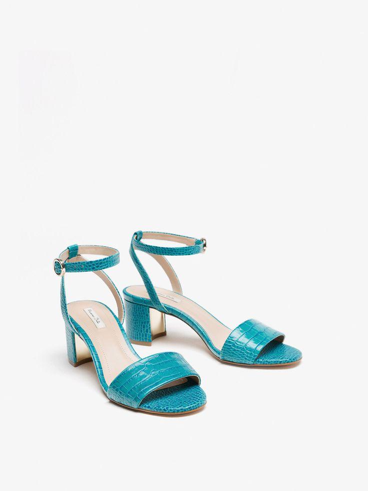 Sandale à talon moyen en cuir, finition croco turquoise. Pièce métallique à l'avant du talon. Bride cheville avec boucle sur le côté.