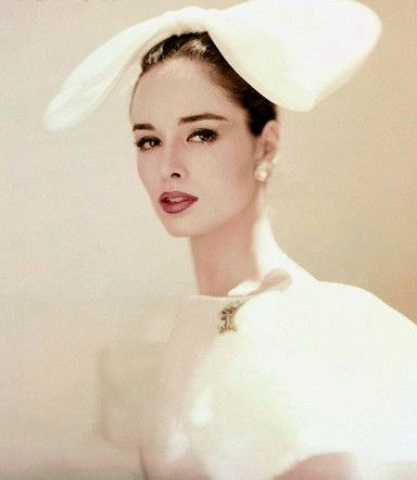 Sondra Peterson 1960.  Sondra is wearing a white organdie hair bow and matching overblouse, pinned at the collar with a Verdura jewel. The dress is from Jax and the bow is from Adolfo of Emme.