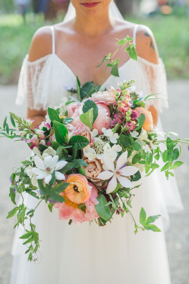 Beautiful summer bridal bouquet of coral charm peonies, clematis, passion vine, ranunculus and foxglove by Haute Blossoms Floral. Image by Trevor- Captivated Studios.