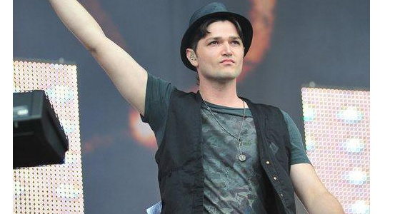 Pictured on the V Festival stage, Danny O'Donoghue sticks to his usual attire of a graphic tee, bowler hat and casual waistcoat.