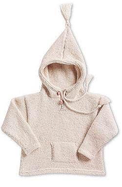 En fin råhvid hættebluse med lomme og kvaster strikket i blød økologisk uld.