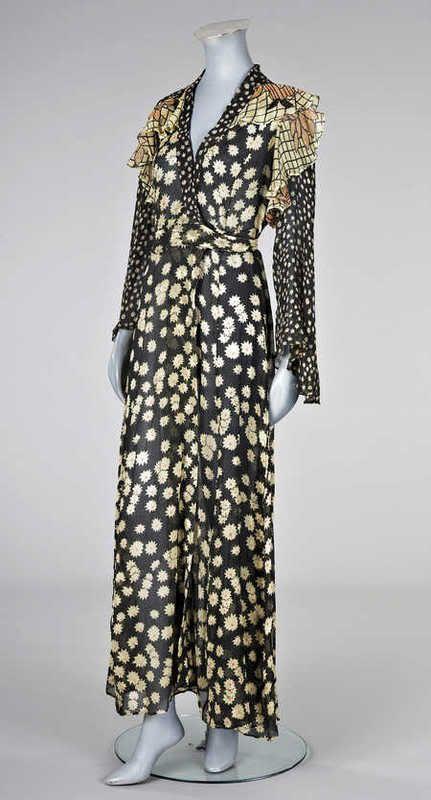 ossie clark and Celia Birtwell, 1970.  Floor length, long sleeved, black chiffon pattern wrap dress.