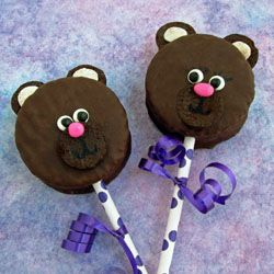 Add cookies and candies to a chocolate snack cake to create these adorable black bear lollipops.