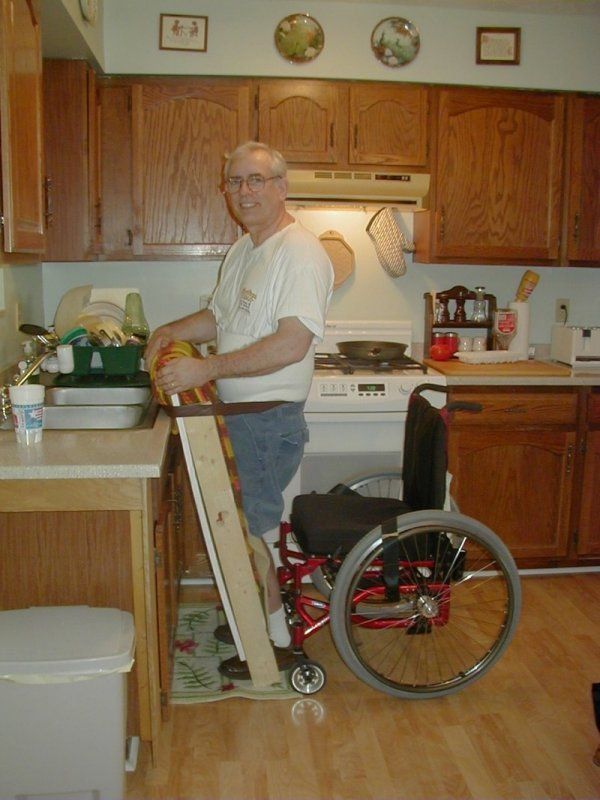 homemade standing aid. Picture shows how this aid helps this man with a physical disability stand up to wash his hands.