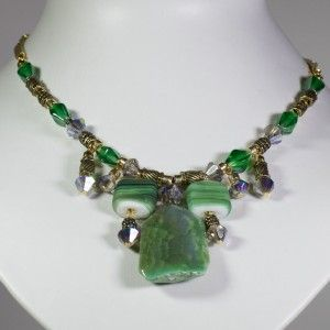 Elegant necklace of green semi-precious centerpiece accompanied by Swarovski crystals, beads and gold-plated pieces