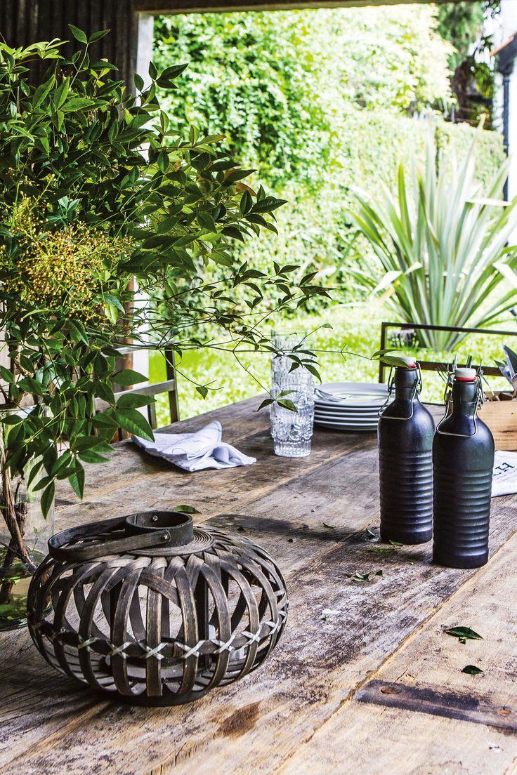 Detalle de una mesa rústica hecha con tablones de lapacho gris (Pablo Ledesma) del quincho de esta casa con jardín. En ella, botellas para agua, fanal de hierro y vaso de vidrio.