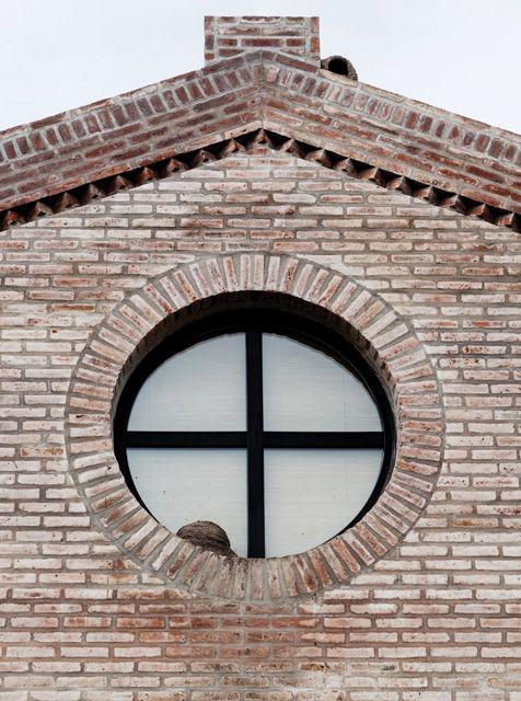 Detalle de la fachada de una casa de campo en Chascomús que replica las formas de un viejo galpón ferroviario con ladrillo visto y gran ventana ojo de buey.