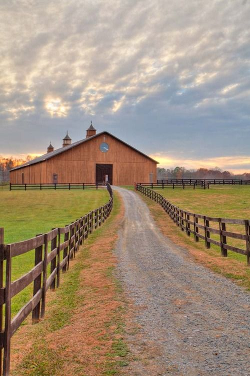 barn with a long drive way and pastures along side.
