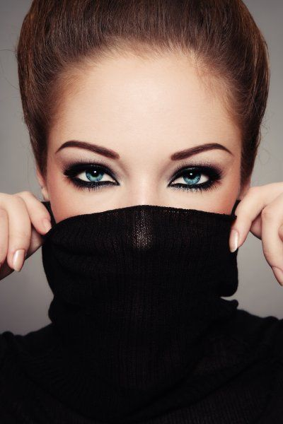 Fashion brunette woman with magnetic green eyes and trendy  make up wearing a black pullover