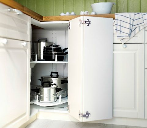 An close up of an opened corner cabinet filled with pots and pans on a rotating shelf in a white kitchen.