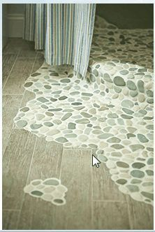 Green and white pebble tile flooring and shower floor transition
