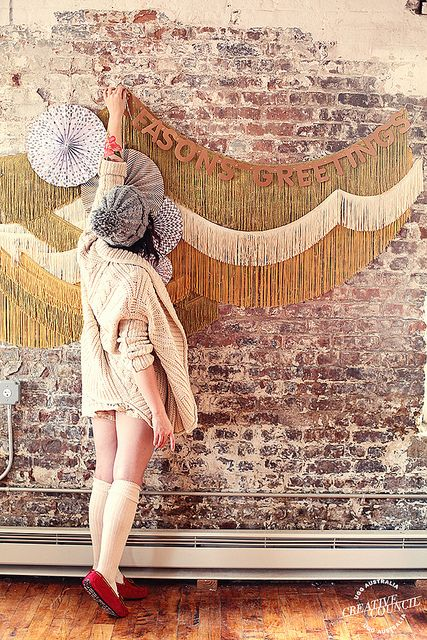 Keiko Lynn: I draped different colors and lengths of fringe on the brick wall. Then draped some store bought decor over the top. This also worked as a fantastic backdrop for pictures.