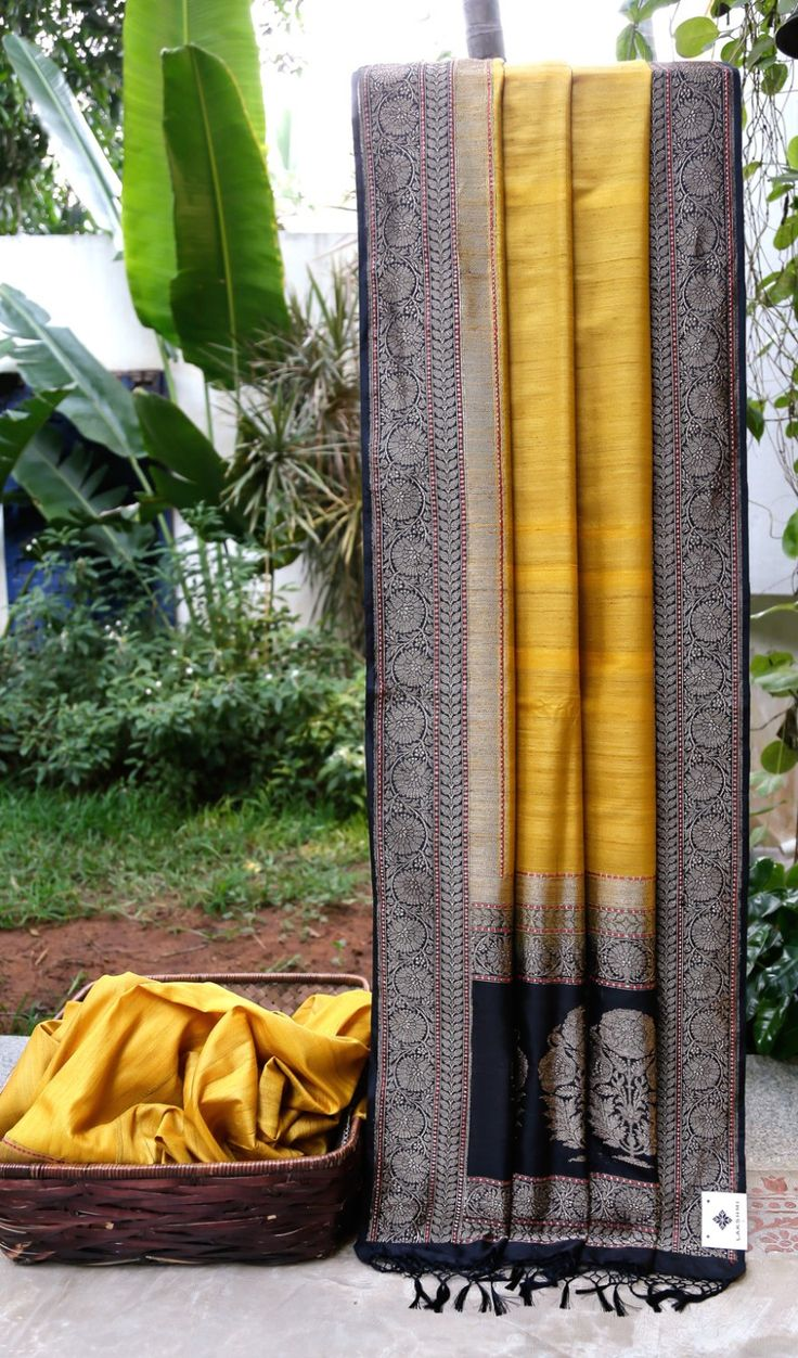 This Benares tussar is in a medallion yellow colour. The border and pallu are in ink black with a pattern in gold zari and crimson red thread work giving it a sophisticated look