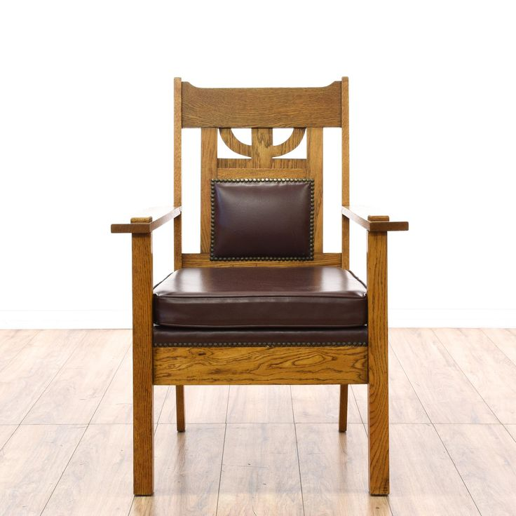 This mission style armchair is featured in a solid wood with a rustic oak finish. This craftsman accent chair has a carved back with dark red leather upholstered cushions, nailhead trim and joinery details. Stunning statement piece perfect for accenting a room! #americantraditional #chairs #armchair #sandiegovintage #vintagefurniture