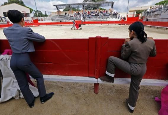 Solal (L), 12, and Nino, 10, both toreador apprentices of the Nimes bullfighting school, look at a beginner's bullfight (becerrada) at the bullring of Bouillargues, near Nimes, October 5, 2013.  REUTERS/Jean-Paul Pelissier